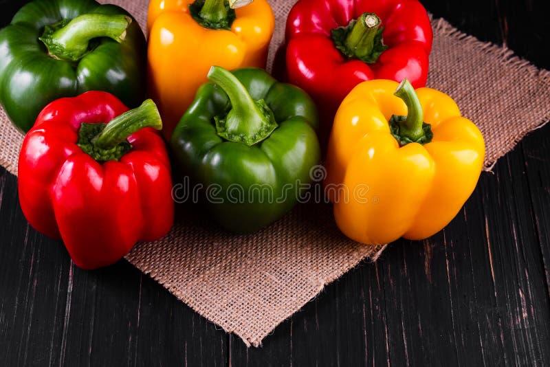 Tre söta peppar på en träbakgrund som lagar mat grönsaksallad fotografering för bildbyråer