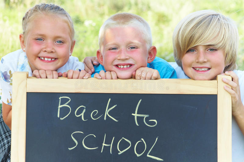 Tre scolari immagine stock