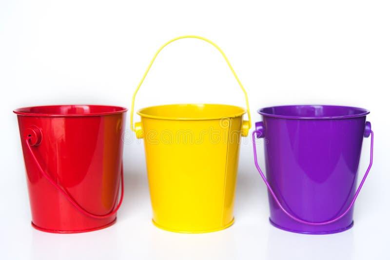 Tre secchi del metallo hanno colorato condizione rossa, gialla e porpora nella fila contro fondo bianco solido immagine stock