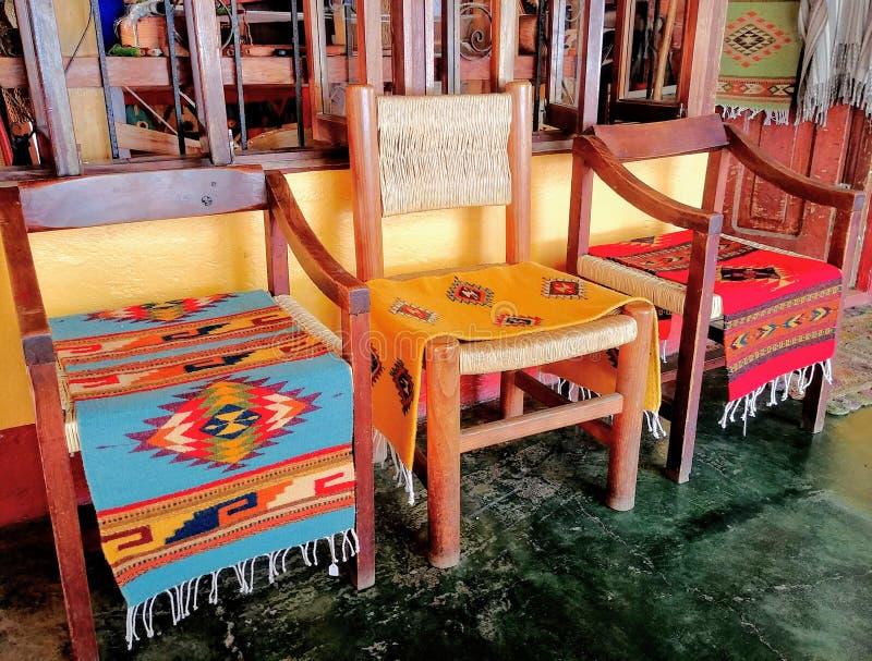 Tre sedie di legno con le coperte tessute a mano modellate variopinte ad un negozio dell'artigiano nel Messico fotografie stock libere da diritti