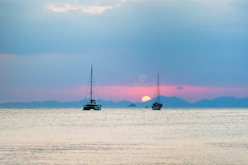 Tre segla yachter i havet Under solnedgång ställer solen in över bergen royaltyfria foton