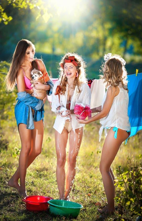 Tre sexiga kvinnor med provokativa dräkter som sätter kläder för att torka i sol Sinnliga unga kvinnlig som skrattar sätta ut tva arkivfoton