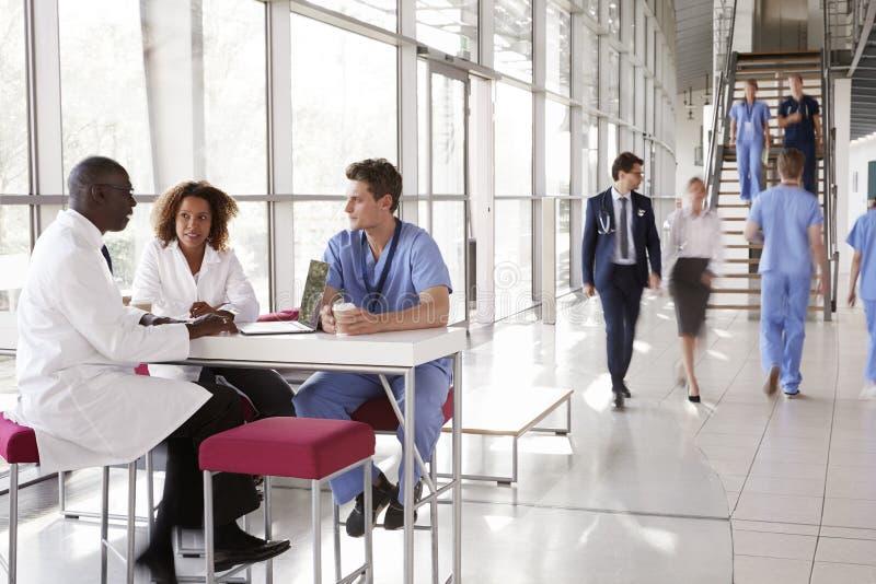 Tre sjukvårdarbetare som talar i en upptagen modern lobby arkivfoton