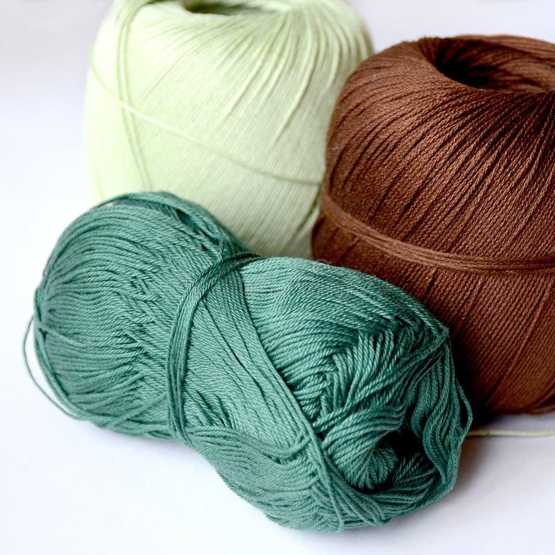 Tre skeins för att sticka brunt mörkt - grönt och ljust - grönt arkivfoto