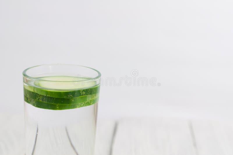 Tre skivor av grön ny gurka i exponeringsglas med vatten på gamla träplankor royaltyfri bild