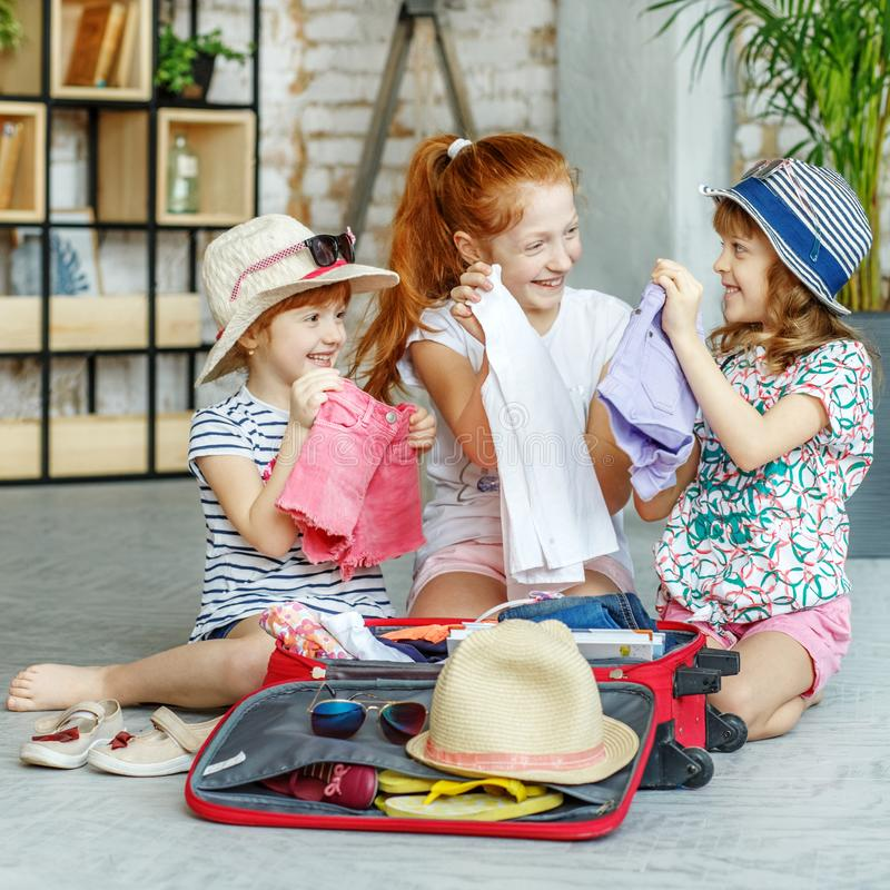 Tre små flickor packade deras kläder i en resväska Begrepp, royaltyfri foto