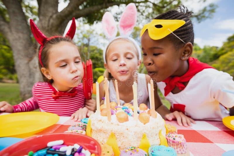 Tre små flickor som tillsammans blåser födelsedagstearinljus royaltyfri bild