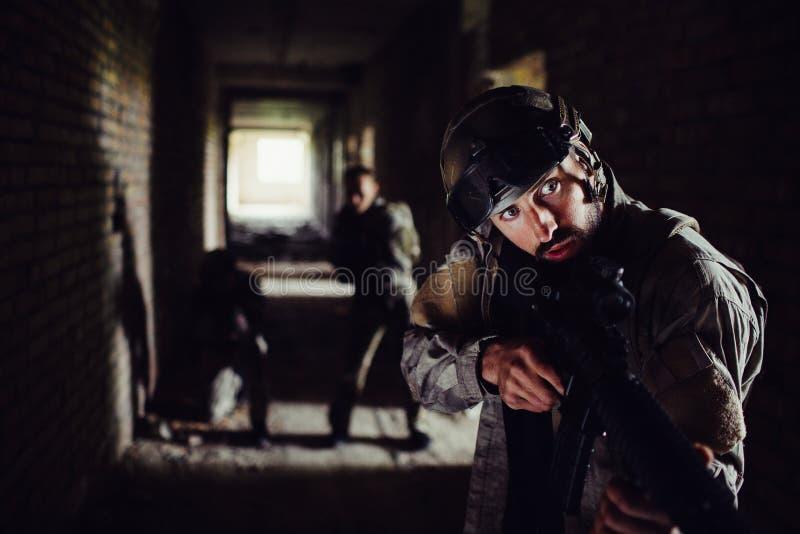 Tre soldater står, i mörk korridor och att vänta Grabben ser framme till rätt- och innehavgeväret in fotografering för bildbyråer