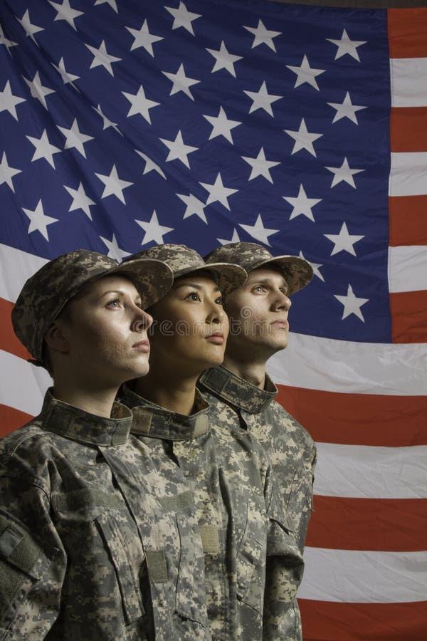 Tre soldati posati davanti alla bandiera americana, veritcal fotografie stock libere da diritti