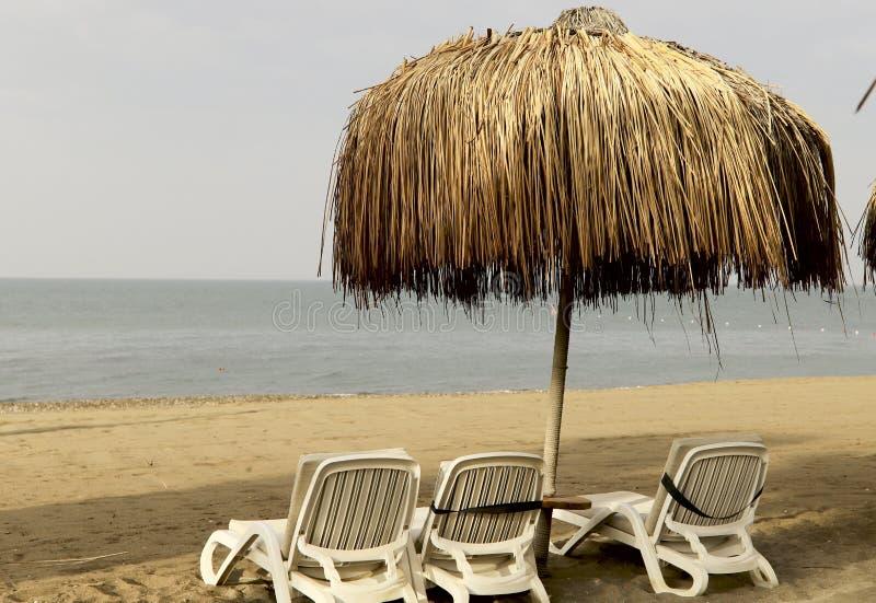 Tre solstolar under ettskydd paraply som göras av torrt gräs på stranden mot bakgrunden av havet arkivbild
