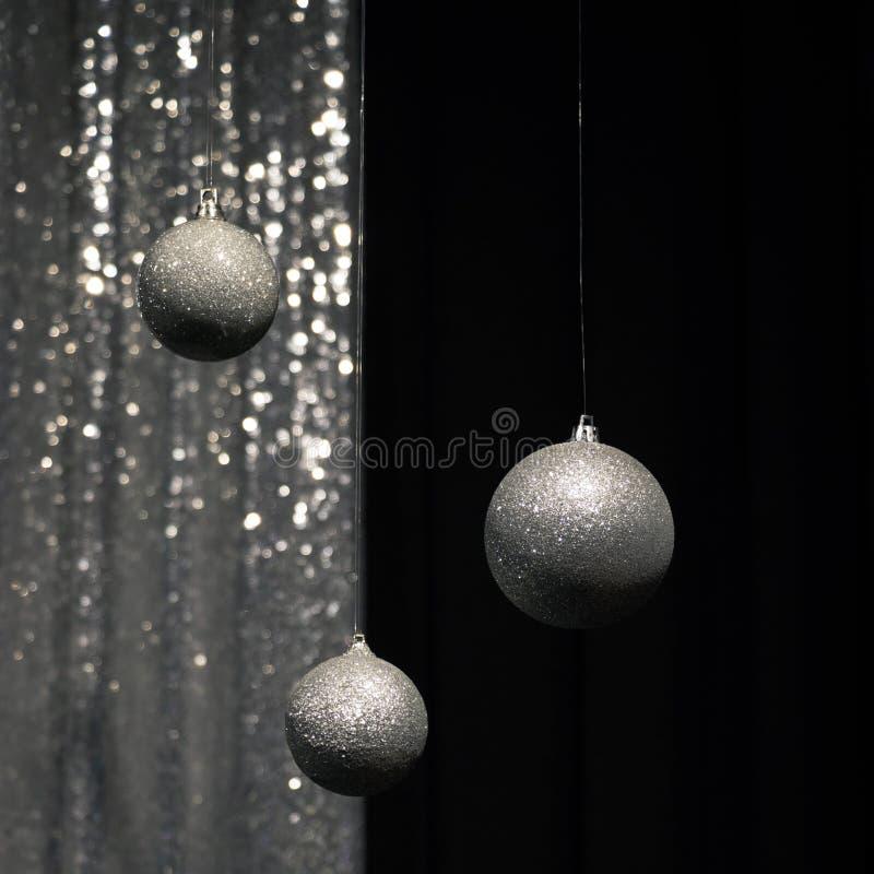 Tre som hänger, försilvrar julbollar på mörkt och försilvrar bakgrund arkivbilder