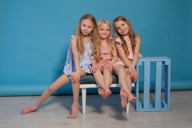 Tre sorelle alla moda delle amiche delle ragazze mangiano il dolce della lecca-lecca della caramella immagini stock