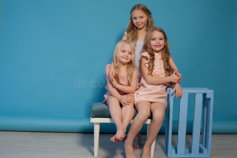Tre sorelle alla moda delle amiche delle ragazze mangiano il dolce della lecca-lecca della caramella fotografia stock libera da diritti