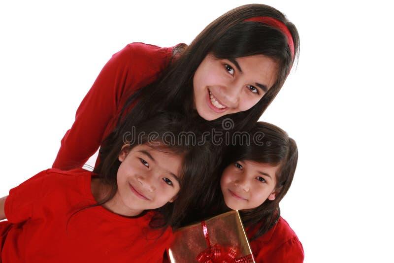 Tre sorelle che tengono i presente fotografia stock libera da diritti