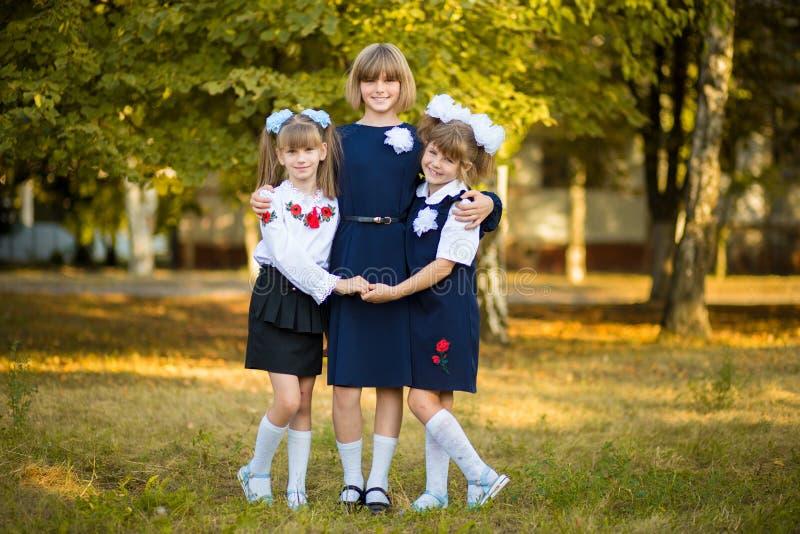 Tre sorelle felici abbracciano insieme nel parco di autunno in uniforme scolastico immagini stock libere da diritti