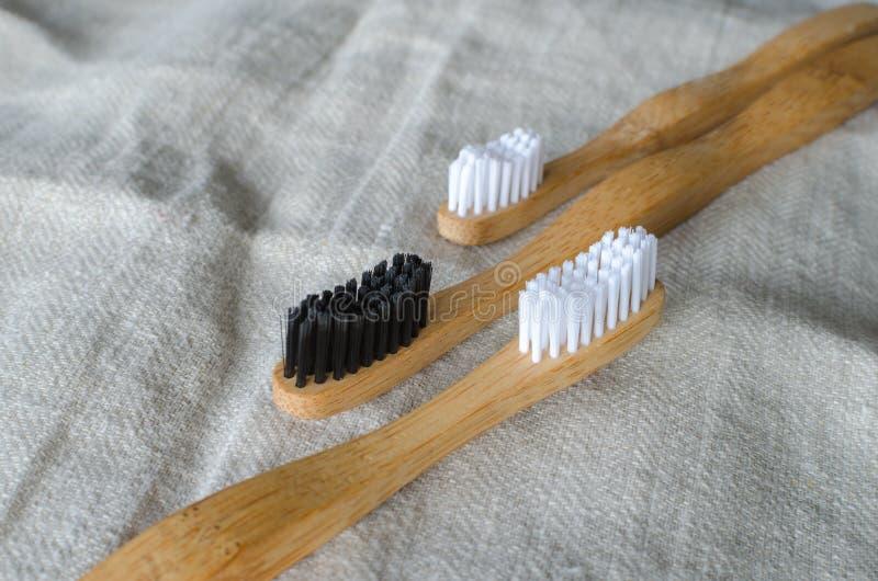 Tre spazzolini da denti di bambù sul fondo grigio del tessuto Copi lo spazio per testo immagine stock libera da diritti
