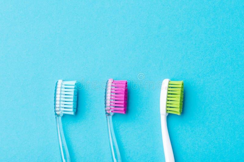 Tre spazzolini da denti variopinti di plastica su un fondo blu, fine su fotografie stock libere da diritti