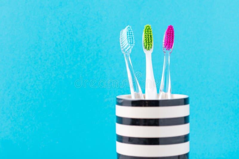 Tre spazzolini da denti variopinti di plastica in vetro su un fondo blu, fine su fotografia stock