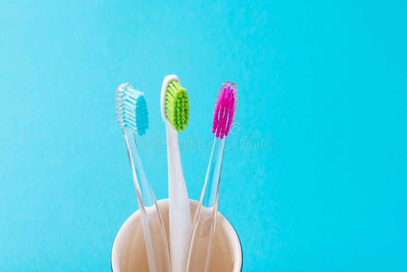 Tre spazzolini da denti variopinti di plastica in vetro su un fondo blu, fine su immagine stock