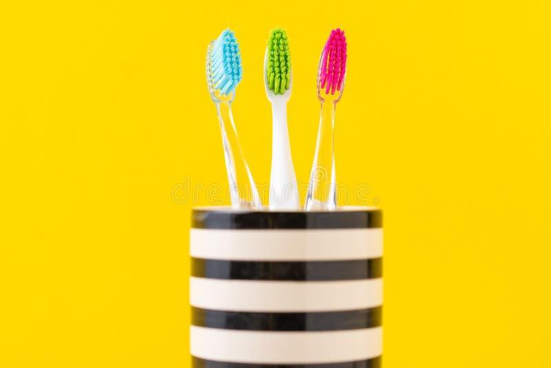 Tre spazzolini da denti variopinti di plastica in vetro su un fondo giallo, fine su immagine stock