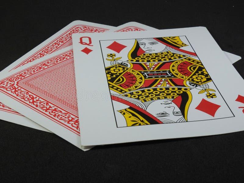 Tre spela kort Drottningen av diamanter vänder mot upp royaltyfria foton