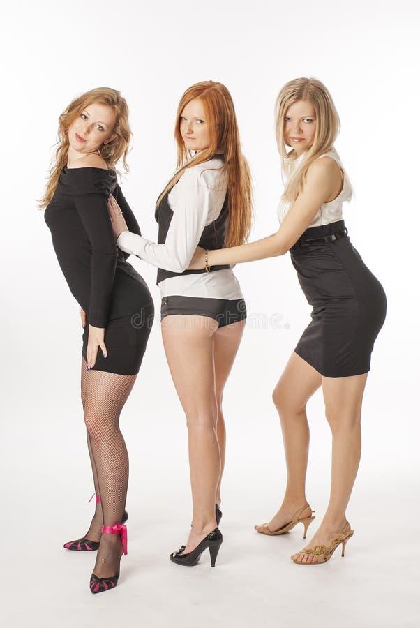 Tre spensliga flickor på vit bakgrund royaltyfria bilder