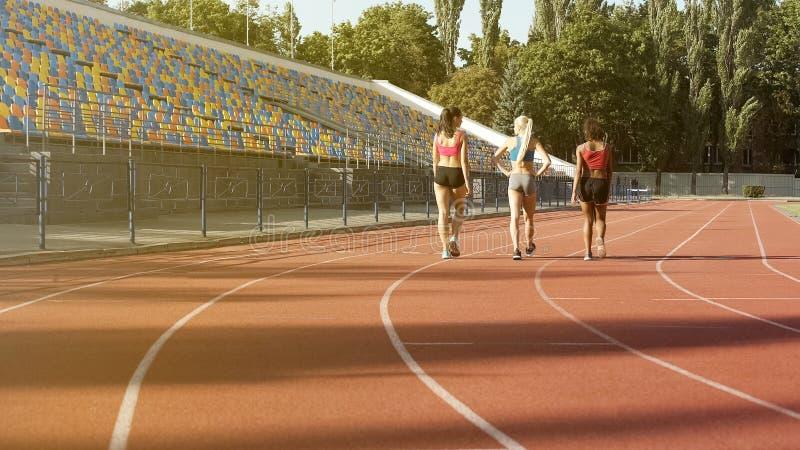 Tre sportive flickor som går på stadionspår, når de har övat, team att koppla av royaltyfria bilder