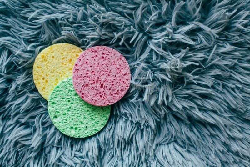 Tre spugne colorate per lavare il vostro fronte fotografia stock libera da diritti