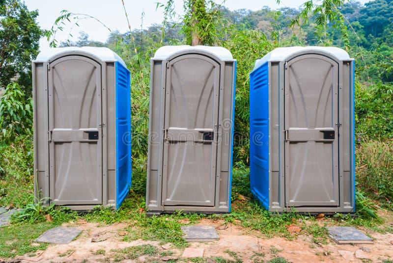 Tre stanze della toilette mobile di plastica pubblica in foresta immagine stock libera da diritti