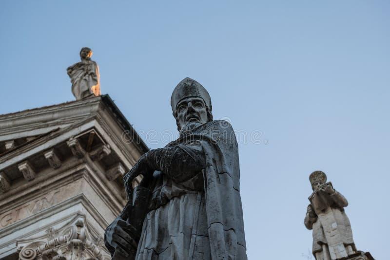 Tre statyer av klosterbroder marmorerar diagram n?ra den huvudsakliga kyrkan av Urbino, Italien arkivfoto