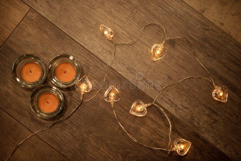Tre stearinljus och hjärta formad dekorativ rad för elljus på pläterat trägolv arkivbilder
