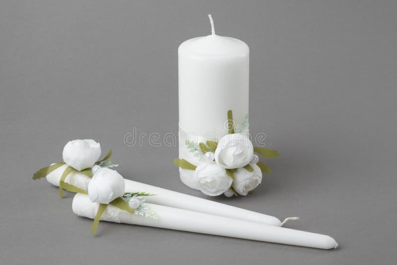 Tre stearinljus som dekoreras med vita rosor på grå bakgrund arkivbilder