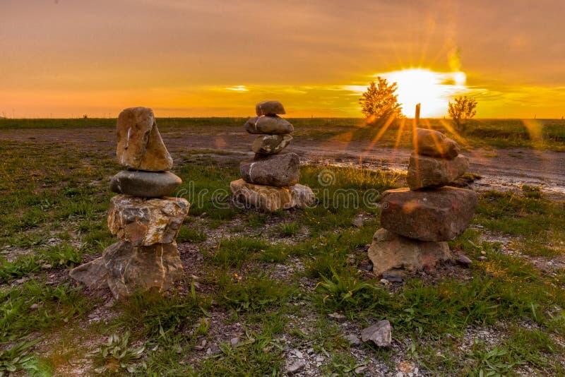 Tre stenar pelare med en fantastisk solnedg?ng i baksidan av nationalparken Waterschei i Genk royaltyfri bild