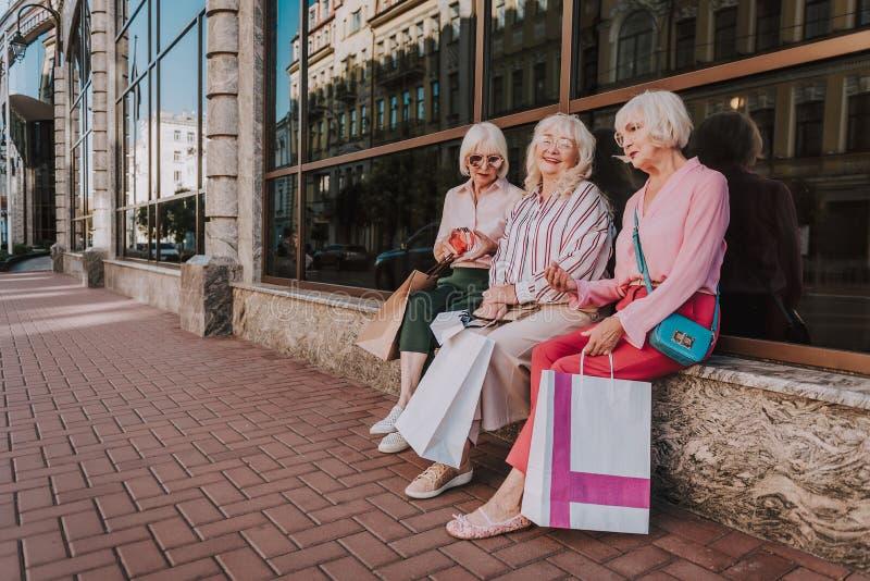 Tre stilfulla kvinnliga pensionärer sitter nära galleria arkivbild