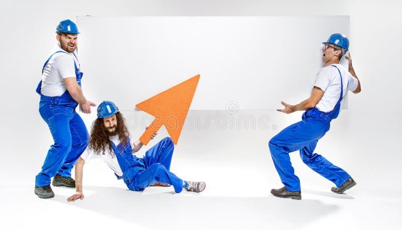 Tre stiliga hantverkare som rymmer ett tomt vitt bräde fotografering för bildbyråer