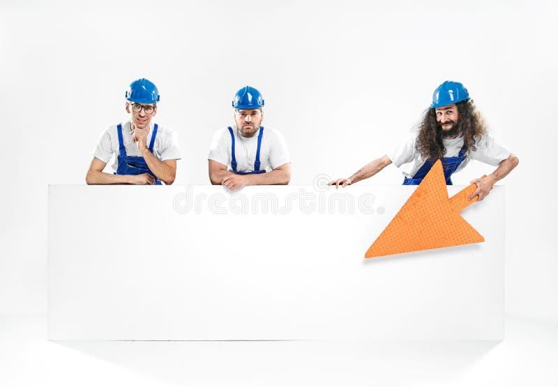 Tre stiliga hantverkare som rymmer ett tomt vitt bräde arkivbilder
