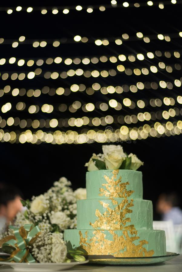 tre strati del dolce di colore verde con la rosa di bianco sulla cima e sul beautif fotografie stock
