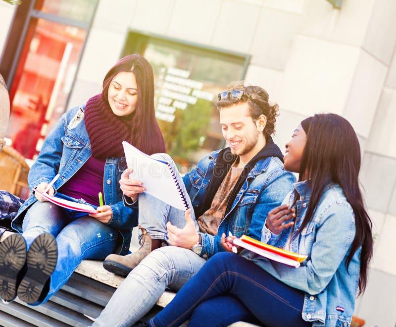 Tre studenter på en bänk utomhus arkivbilder