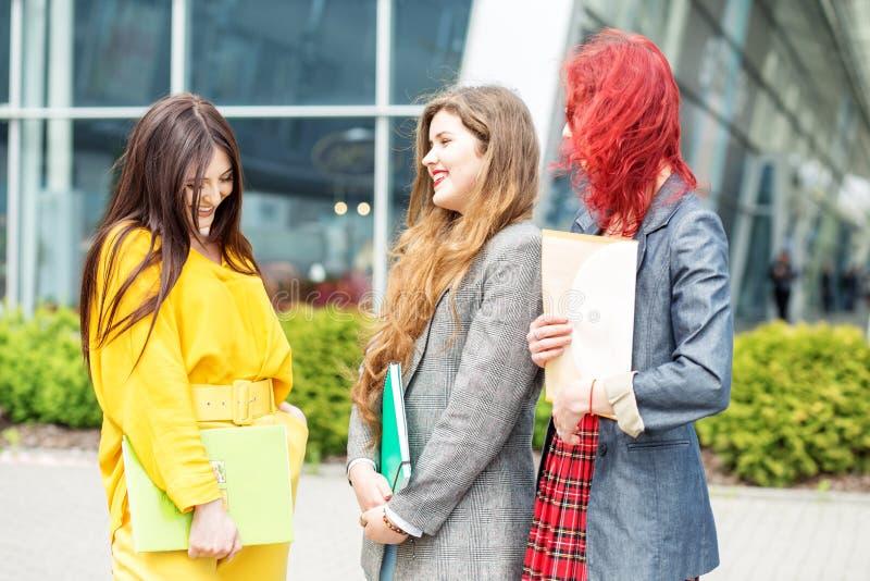 Tre studenter talar och skrattar på universitetet Utbildningsbegrepp, kamratskap och grupp m?nniskor arkivfoton