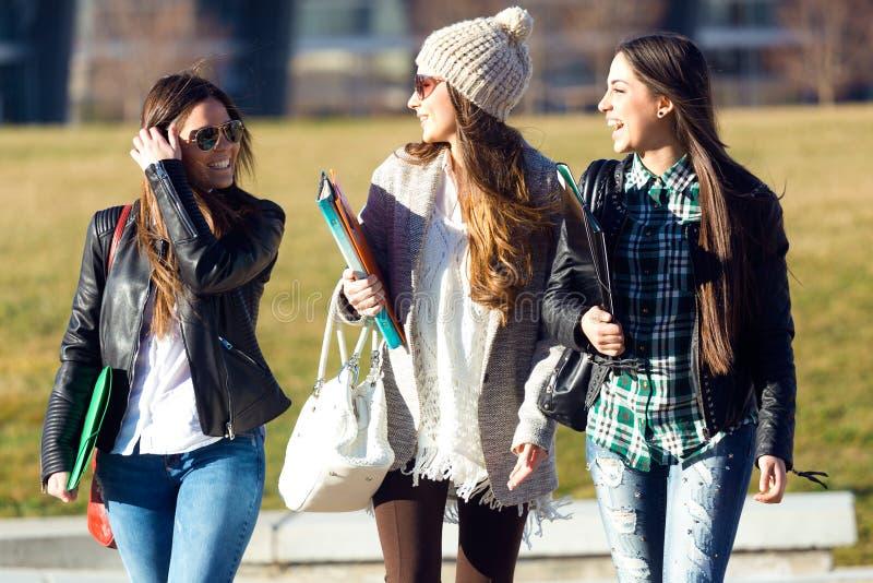 Tre studentflickor som går i universitetsområdet av universitetet arkivbilder
