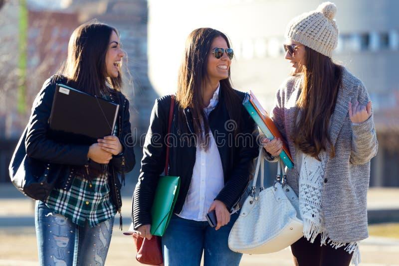 Tre studentflickor som går i universitetsområdet av universitetet royaltyfri bild