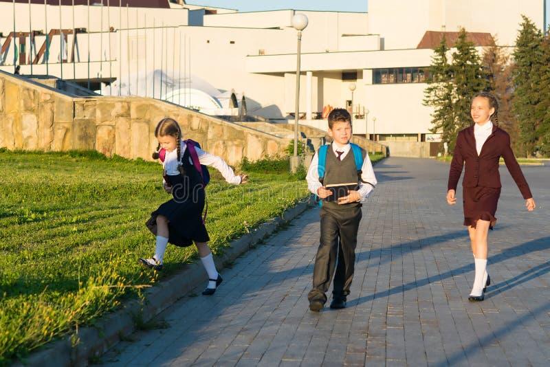 Tre studenti camminano nel parco con le cartelle dopo le classi fotografia stock libera da diritti
