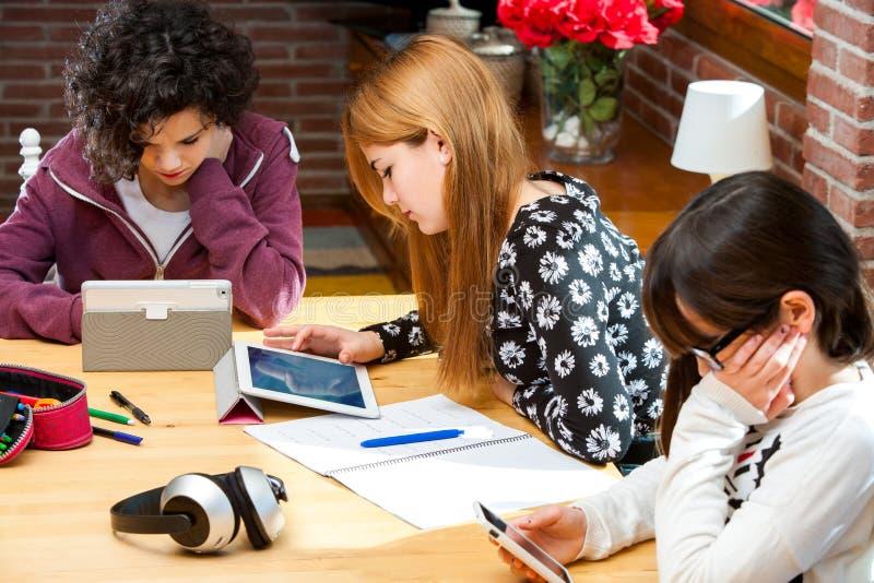Tre studenti che lavorano ai dispositivi digitali. immagini stock