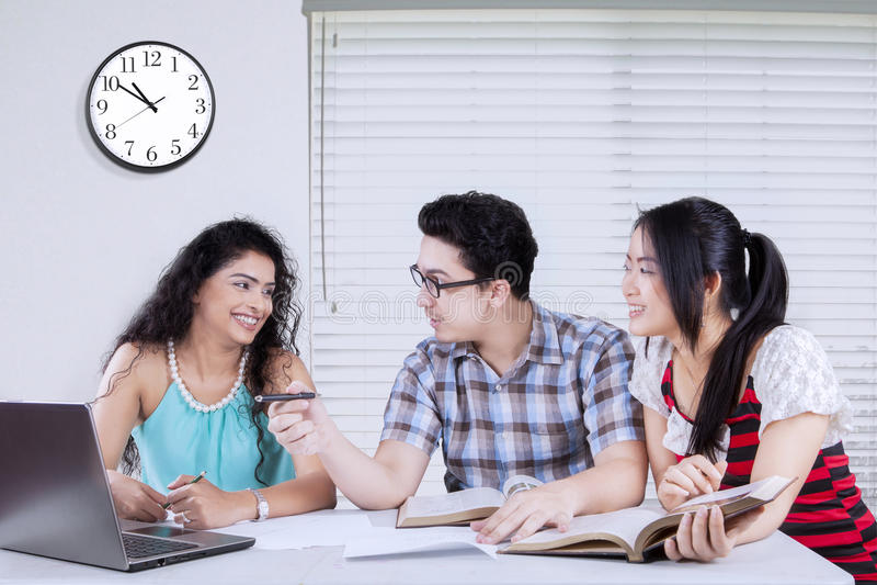 Tre studenti e compiti immagine stock