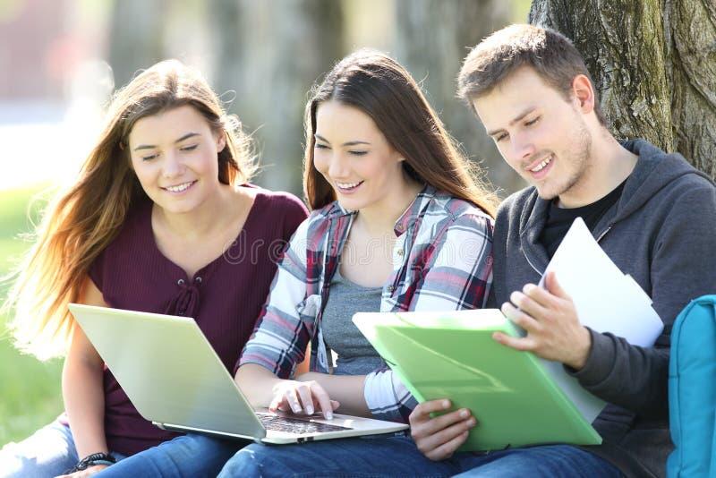 Tre studenti felici che studiano online in un parco fotografia stock libera da diritti