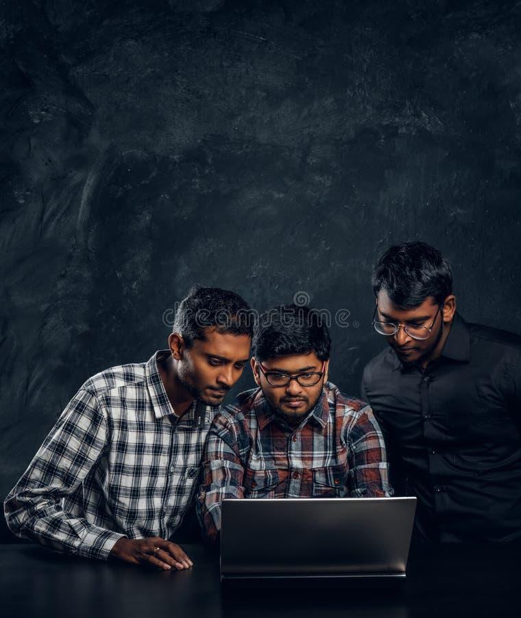 Tre studenti indiani che lavorano ad un progetto che sta insieme alla tavola con un computer portatile immagini stock