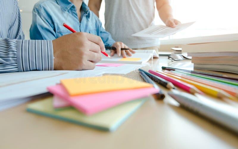 Tre studenti sicuri che fanno insieme compito mentre sedendosi a casa immagine stock libera da diritti