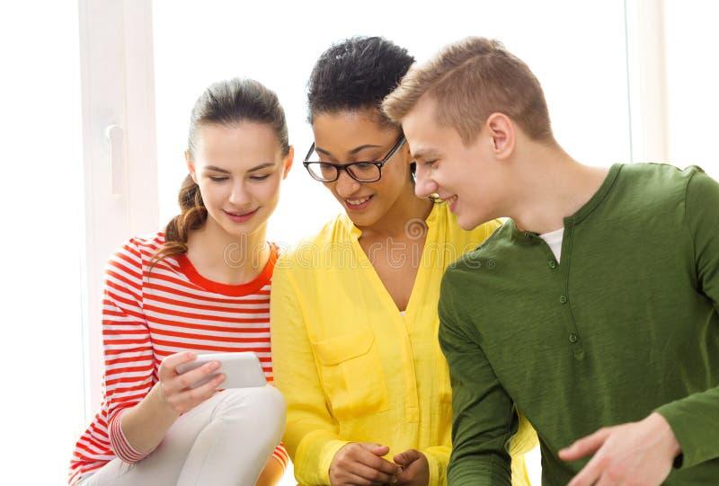 Tre studenti sorridenti con lo smartphone alla scuola fotografia stock