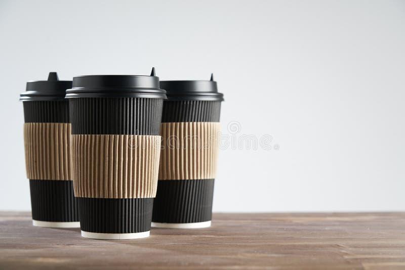 Tre svarta kopp för pappers- disponibelt kaffe för tagande bort eller att gå, på trätabellen, utrymme för designorientering royaltyfri fotografi