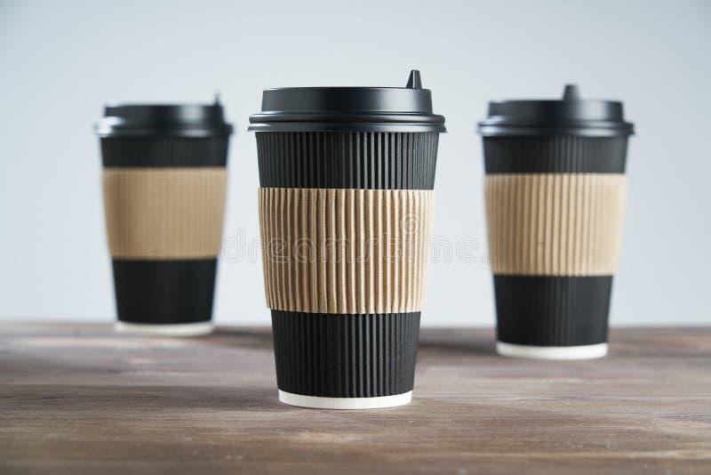 Tre svarta kopp för pappers- disponibelt kaffe för tagande bort eller att gå, på trätabellen, utrymme för designorientering arkivbilder